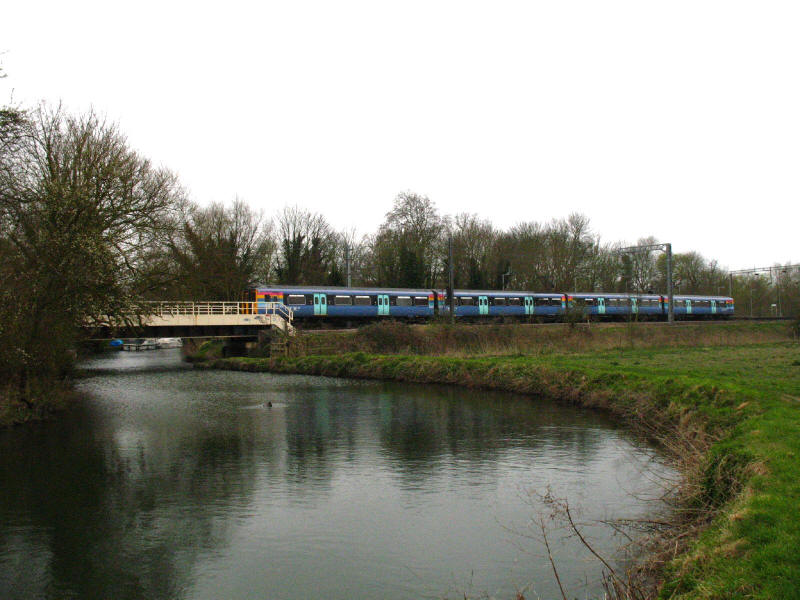 Roydon station and One Railway train over River Stort
