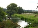 A narrowboat makes its way along the River Nene with a Nene Valley Railway train behind